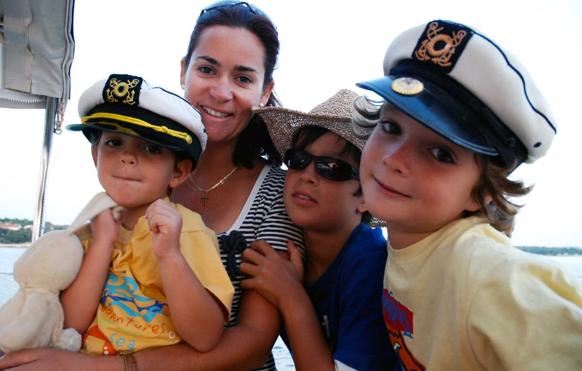 smiling mum with 3 cute little boys in captain hats on a boat
