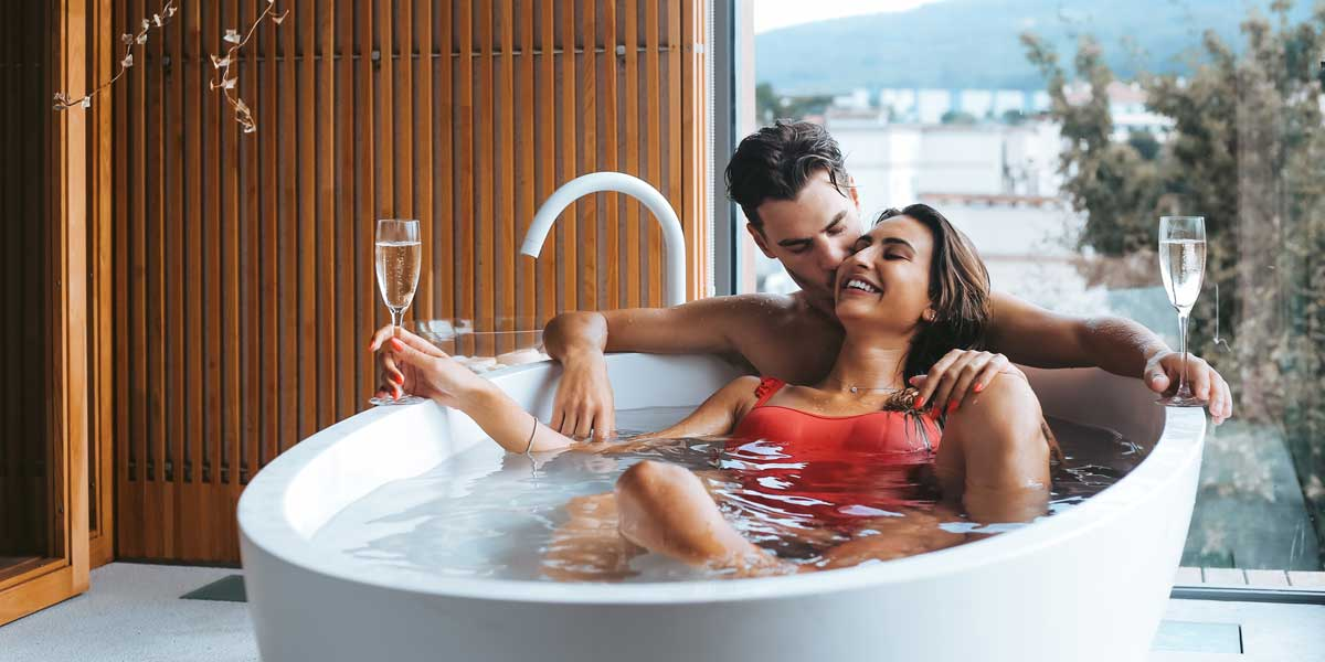 Beautiful loving couple sitting in a fancy hotel bathtub in front of a giant window enjoying 2 glasses of prosecco