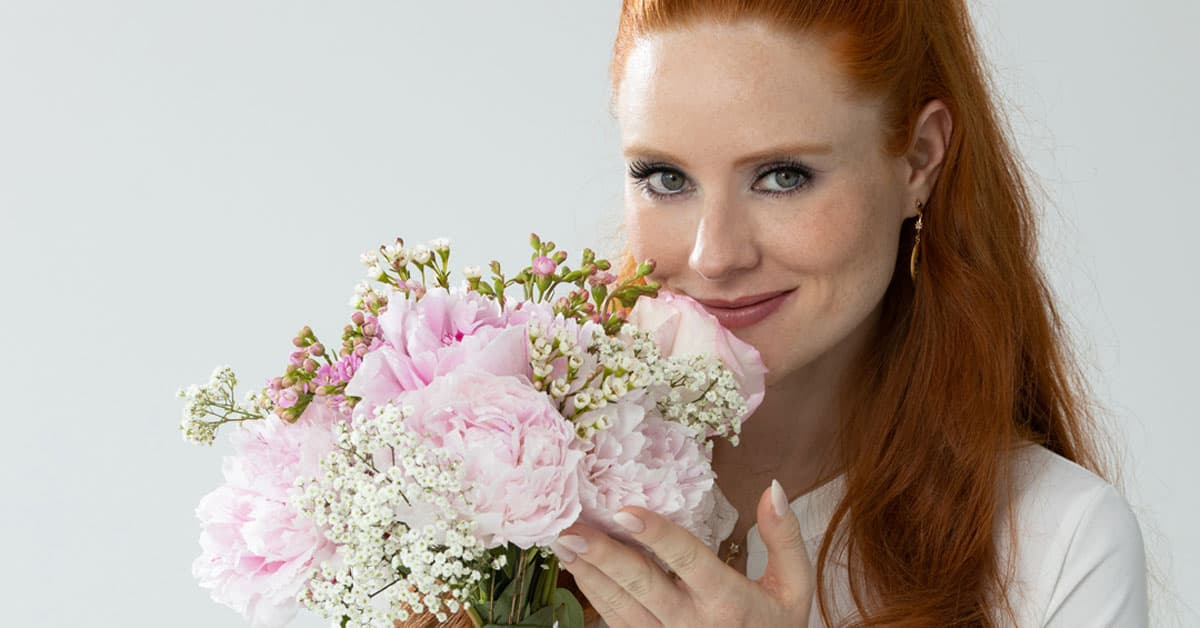 Model and femSense Ambassador Barbara Meier smelling a beautiful bunch of flowers